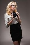 Blondes Mädchen mit tragenden Brillen der Kamera Stockbilder
