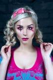 Schönes blondes Mädchen mit zwei Zöpfen, mit kreativem Puppenmake-up: rosa glatte Lippen, tragendes rosa skeleton Kleid für das H Stockbild
