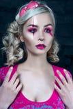 Schönes blondes Mädchen mit zwei Zöpfen, mit kreativem Puppenmake-up: rosa glatte Lippen, tragendes rosa skeleton Kleid für das H Lizenzfreie Stockfotografie