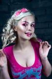 Schönes blondes Mädchen mit zwei Zöpfen, mit kreativem Puppenmake-up: rosa glatte Lippen, tragendes rosa skeleton Kleid für das H Lizenzfreies Stockfoto
