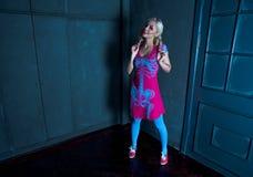 Schönes blondes Mädchen mit zwei Zöpfen, mit kreativem Puppenmake-up: rosa glatte Lippen, tragendes rosa skeleton Kleid, werfend  Lizenzfreie Stockfotografie