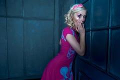 Schönes blondes Mädchen mit zwei Zöpfen, mit kreativem Puppenmake-up: rosa glatte Lippen, tragendes rosa skeleton Kleid, werfend  Stockbild