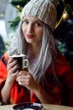 Schönes blondes Mädchen in pom pom Hut und im roten Schal mit den Weinrotlippen den Kaffee, die Kamera betrachtend trinkend Lizenzfreies Stockfoto