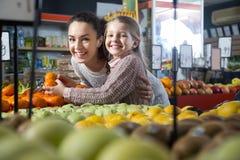 Schönes blondes Mädchen Portret mit der Mutter, die Mandarinen an wählt Lizenzfreies Stockfoto