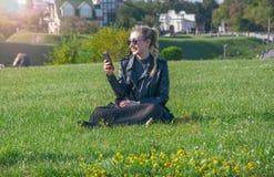 Schönes blondes Mädchen sitzt auf einem grünen Rasen und schaut in einem Smartphone Lizenzfreie Stockfotografie