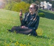 Schönes blondes Mädchen sitzt auf einem grünen Rasen und schaut in einem Smartphone Stockfoto
