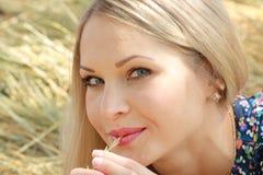Schönes blondes Mädchen sitzt auf Weizen Stockfotografie