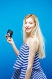 Schönes blondes Mädchen in Sommer gestreiftem Kleid mit Retro- Kamera auf blauem Hintergrund im Studio Stockbilder