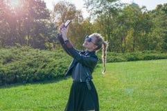Schönes blondes Mädchen steht auf einem grünen Rasenhintergrund und macht selfie Lizenzfreies Stockbild