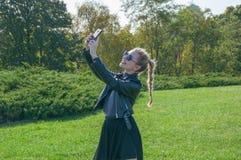 Schönes blondes Mädchen steht auf einem grünen Rasenhintergrund und macht selfie Stockbilder