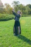 Schönes blondes Mädchen steht auf einem grünen Rasenhintergrund und macht selfie Lizenzfreies Stockfoto