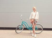 Schönes blondes Mädchen steht nahe dem Weinlesefahrrad mit brauner Weinlesetasche haben den Spaß und gute Laune, die in camera sc Lizenzfreies Stockfoto