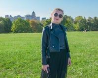 Schönes blondes Mädchen steht und lächelt auf dem grünen Rasenhintergrund Stockbilder