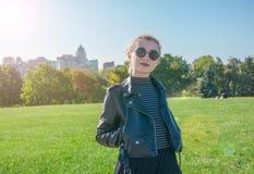 Schönes blondes Mädchen steht und lächelt auf dem grünen Rasenhintergrund Lizenzfreies Stockfoto