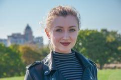 Schönes blondes Mädchen steht und lächelt auf dem grünen Rasenhintergrund Stockfoto