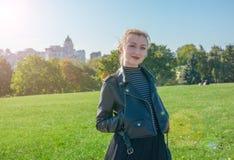 Schönes blondes Mädchen steht und lächelt auf dem grünen Rasenhintergrund Lizenzfreie Stockfotografie