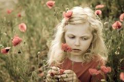 Schönes blondes Mädchen und rote Mohnblumenblumen Lizenzfreie Stockfotos