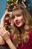 Schönes blondes Mädchen vor einem Weihnachtsbaum lizenzfreie stockfotografie