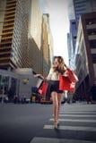 Schönes blondes Mädchen, welches das Einkaufen tut Stockfotografie