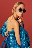 Schönes blondes Mädchen wirft für die Kamera in einer Jacke auf, rückwärts angekleidet Rückseitige Ansicht lizenzfreies stockfoto