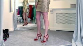 Schönes blondes Mädchen zieht den Vorhang zurück und hat Spaß in einer ShopUmkleidekabine und versucht auf einem blauen und schwa stock video
