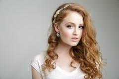 Schönes blondes Mädchenmodell mit großen blauen Augen und gewellter Frisur Stockfotografie