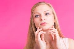 Schönes blondes Mädchenporträt mit den Händen für kosmetisches Konzept über rosa Hintergrund Stockfoto