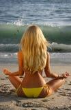 Schönes blondes Meditieren auf dem Strand am Sonnenuntergang Lizenzfreie Stockbilder