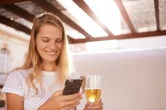 Schönes blondes mit Bier und Mobiltelefon Stockfoto