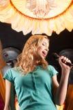 Schönes blondes mit dem Mikrofon, das in der Stange steht Lizenzfreies Stockfoto