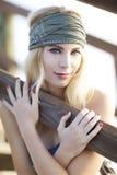 Schönes blondes mit dem Olivgrünstirnband, das auf hölzernem Pier in StAugustine, Florida sitzt Lizenzfreie Stockfotos