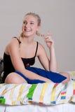Schönes blondes mit großem Lächeln auf Bett Stockbild