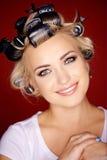 Schönes blondes mit ihrem Haar in den Lockenwicklern Stockfotos
