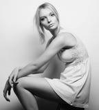 Schönes blondes Modell, das auf einem Schemel sitzt Lizenzfreies Stockbild