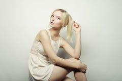 Schönes blondes Modell, das auf einem Schemel sitzt Stockfotografie