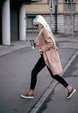 Schönes blondes Modell, das draußen mit Kaffee geht Lizenzfreies Stockbild