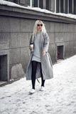Schönes blondes Modell, das draußen mit Kaffee geht Stockbild