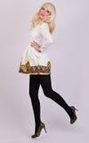 Schönes blondes Modell, das im eleganten Kleid im Studio aufwirft Lizenzfreie Stockfotos