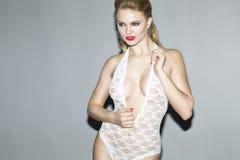 Schönes blondes Modell im Studio, das einen weißen Körperstrumpf trägt Lizenzfreies Stockfoto