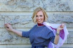 Schönes blondes Modell mit dem Schal, der nahe Steinwand aufwirft Lizenzfreies Stockfoto