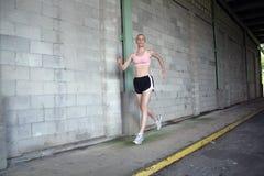 Schönes blondes Rütteln in einer Gasse Lizenzfreie Stockfotos