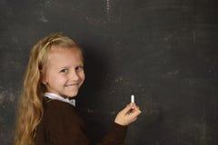 Schönes blondes süßes Schulmädchen in der Uniform, die Kreideschreiben auf dem Tafellächeln glücklich hält Lizenzfreie Stockfotos