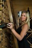 Schönes blondes Sammeln eine Flasche Wein Stockbild