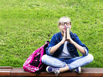 Schönes blondes Schulmädchenmädchen im Jeanshemd ein Buch auf Gras mit einem Rucksack in der Park Bildung lesend Stockfoto