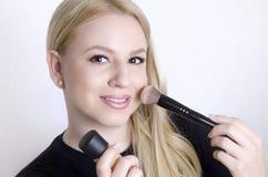 Schönes blondes Setzen auf Make-up Stockfotos