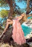 Schönes blondes sexy formschönes weibliches Modell in einem Karnevals-Abendkleid des rosa Ballsaals erstaunlichen, Hochzeit liegt Stockfotografie