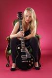 Schönes blondes Sitzen mit E-Gitarre stockfoto