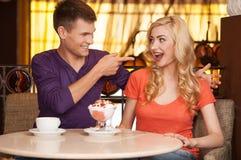 Schönes blondes Sitzen mit Eiscreme auf Nase Stockfoto