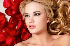 Schönes blondes träumendes Mädchen mit roten Rosen Stockfotografie