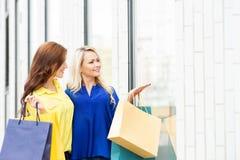 Schönes blondes und Brunette gehend entlang Shopfenster Stockfoto